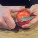 Stap 2: Begin met schillen aan de bovenkant van de tomaat.